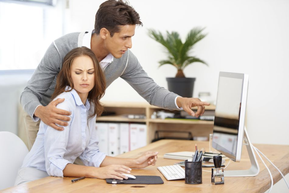 Man with hand on female coworker, as she looks on unapprovingly