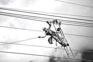 Fitter with ladder, pulling along high-voltage power line