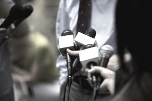 A picture of reporters holding microphones and interviewing someone