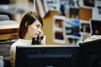 Woman on phone in front of computer
