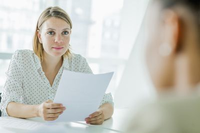 A woman reviews a resume during a job interview.
