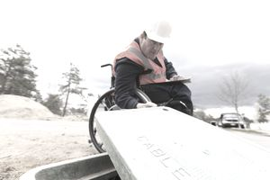 Construction engineer with spinal cord injury inspecting utility box