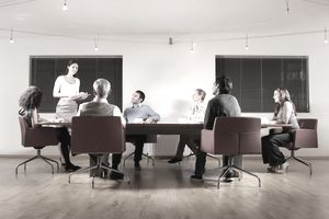 A picture of a person in a meeting with other people