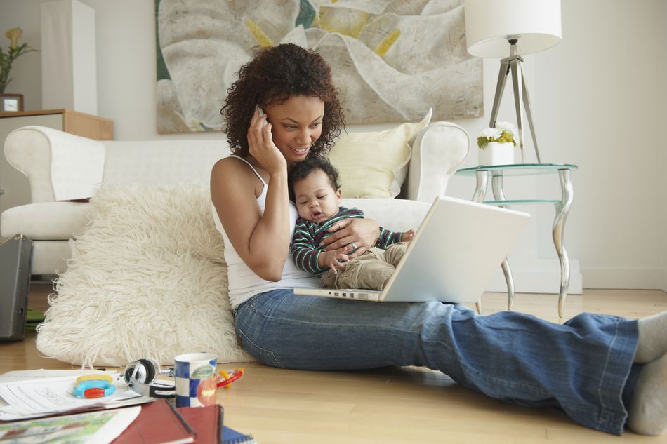 Woman holding baby and using laptop