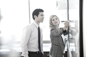 two businesspeople reviewing questions at a whiteboard