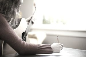Musician Writing Song Lyrics with Guitar