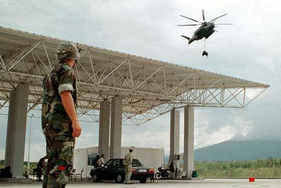 Lance Corporal Duncan M. Mcdonald, a Landing Support Specialist, watching the delivery of supplies from a helicopter.