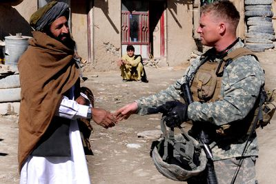 A Civil Affairs Army officer on an assistance mission in Afghanistan shaking hands with local man