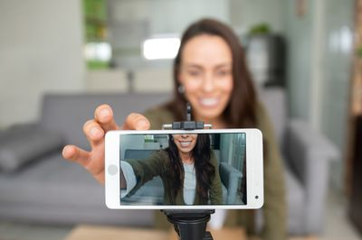 Female recording content at home using her cell phone