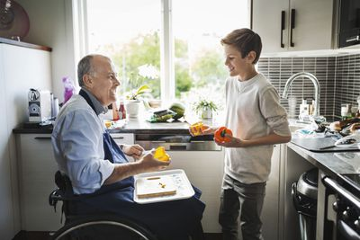 Disabled retiree preparing food with grandson in kitchen