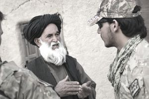 A MAVNI interpreter speaks with a Kandahar local to gather intelligence.