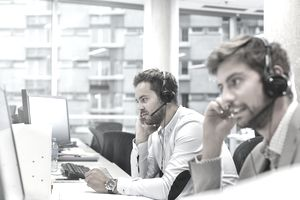 Businessmen with hands-free devices talking on telephone working at computers in office
