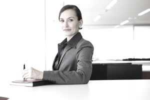 Businesswoman at desk holding pen