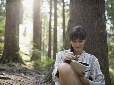 Woman writing dynamic characters with back to tree