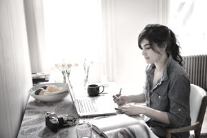 A young woman writing on her computer