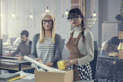 Two young women, a blond and a brunette, are packing up their office coffee cup and papers into a brown box because they were laid off.