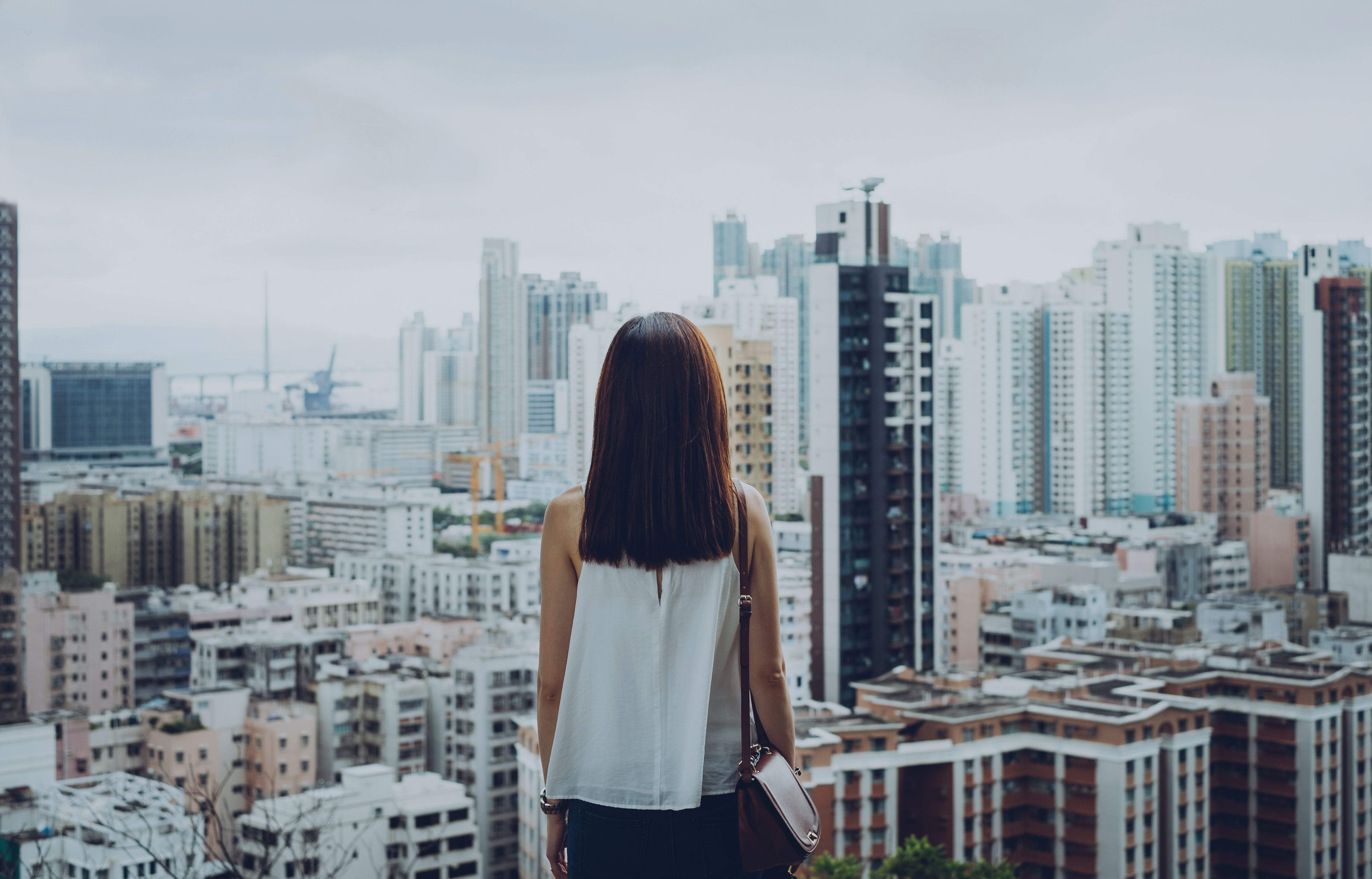 Rear view of woman overlooking busy and energetic cityscape of Hong Kong
