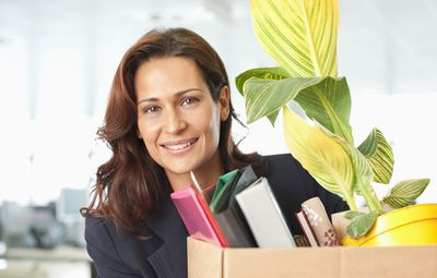 Woman carrying a box of her things out of the office after resigning to go back to school.