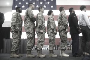 Line of US Military members with flag in background