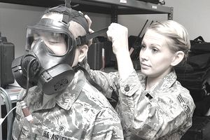 io-environmental engineering technician tightens a gas mask on another airman in Air Force