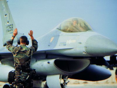 Ground crew signalling to pilot of a military airplane