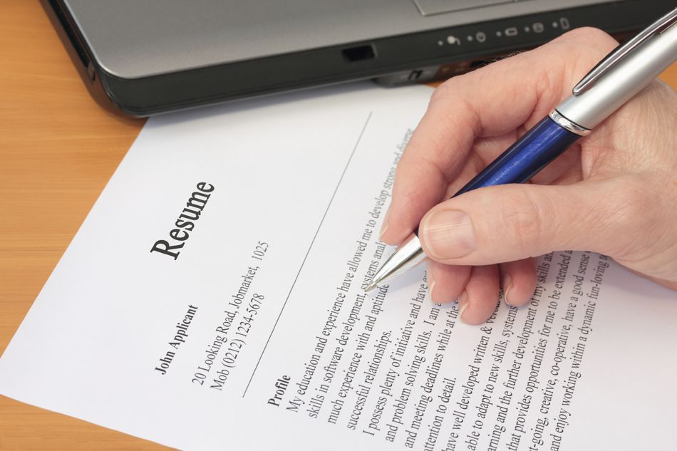 Hand holding a pen proofreading a resume