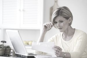 Woman reading mail next to laptop