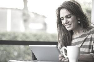 Woman is reading an email and smiling