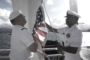 Navy Counselor 1st Class Randy L. Schiller and Senior Chief Navy Counselor George A. Keels, both assigned to the amphibious assault ship USS Boxer (LHD 4), perform a ceremonial flag raising during a visit to the USS Arizona Memorial in Pearl Harbor, Hawaii.