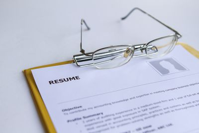 Glasses resting on a resume on a clipboard.