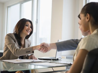 Businesswoman smiling and shaking hands with businessman