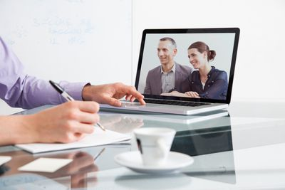 A telecommuter at home participating in a video conference