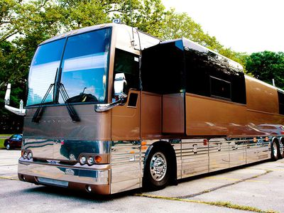 The exterior of a band's luxurious touring bus parked at concert venue.
