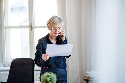 Woman with smartphone working in home office, making a phone call.