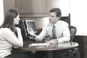 A man and a woman talking at business table