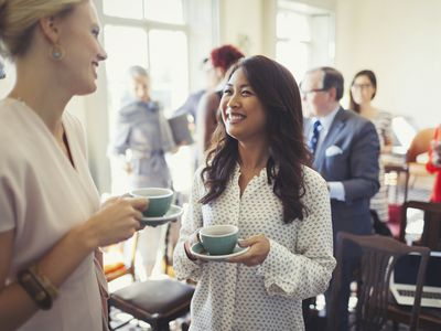 Smiling businesswomen drinking coffee and networking at business conference