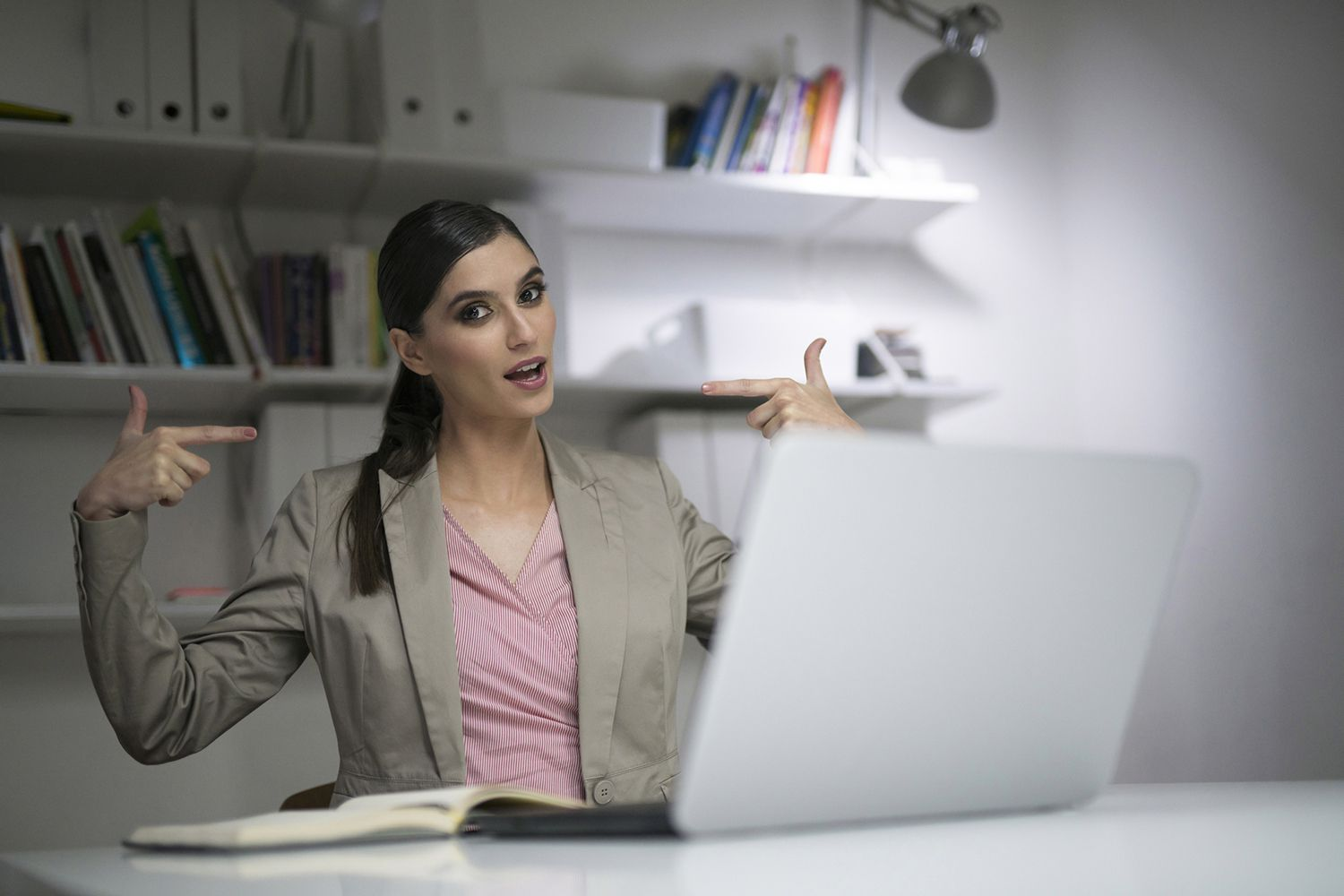 Woman pointing both fingers at herself confidently
