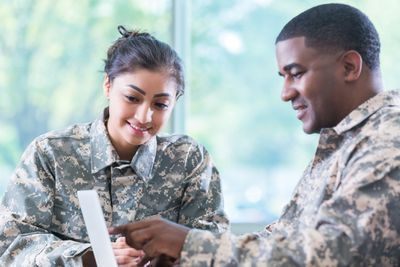 two soldiers looking at a document together