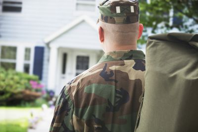 Discharged soldier with bag in front of home