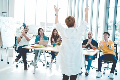 Senior woman showing respect while team applauding congratulating appreciation and employee recognition concept,business successful concept