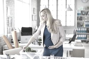 Pregnant woman collecting things at workplace