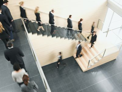 A line of workers streaming down a staircase after a company layoff.