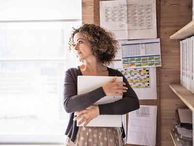 Businesswoman deep in thought and holding a business folder in her arms.