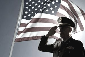 Silhouette of veteran US soldier saluting with an American flag
