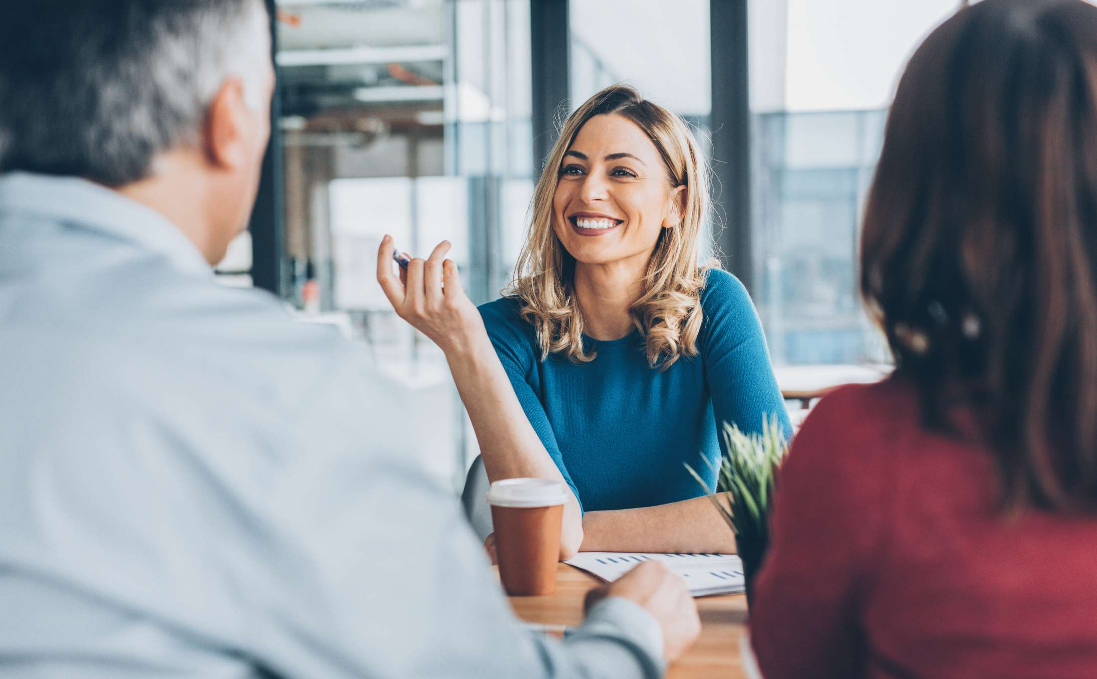 Smiling businesswoman talks to man and woman across desk.