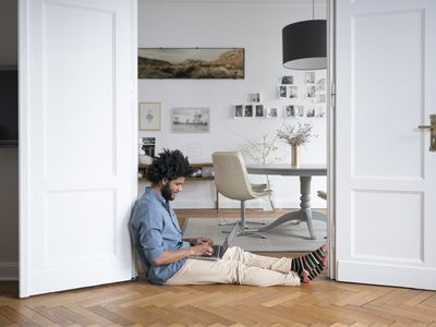 Man sitting on floor working with laptop in door frame working at home.