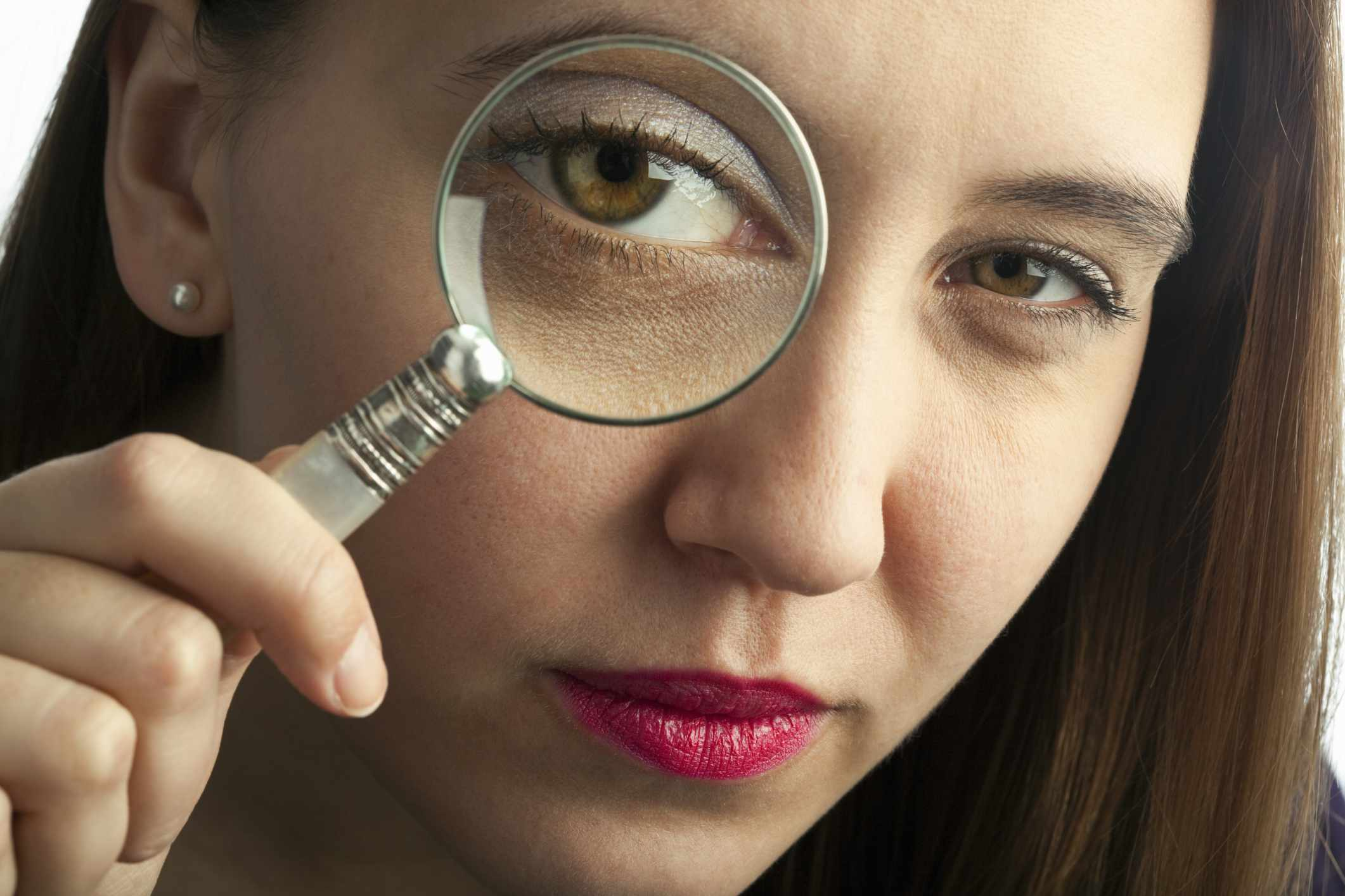 Woman holding a magnifying glass over her eye.