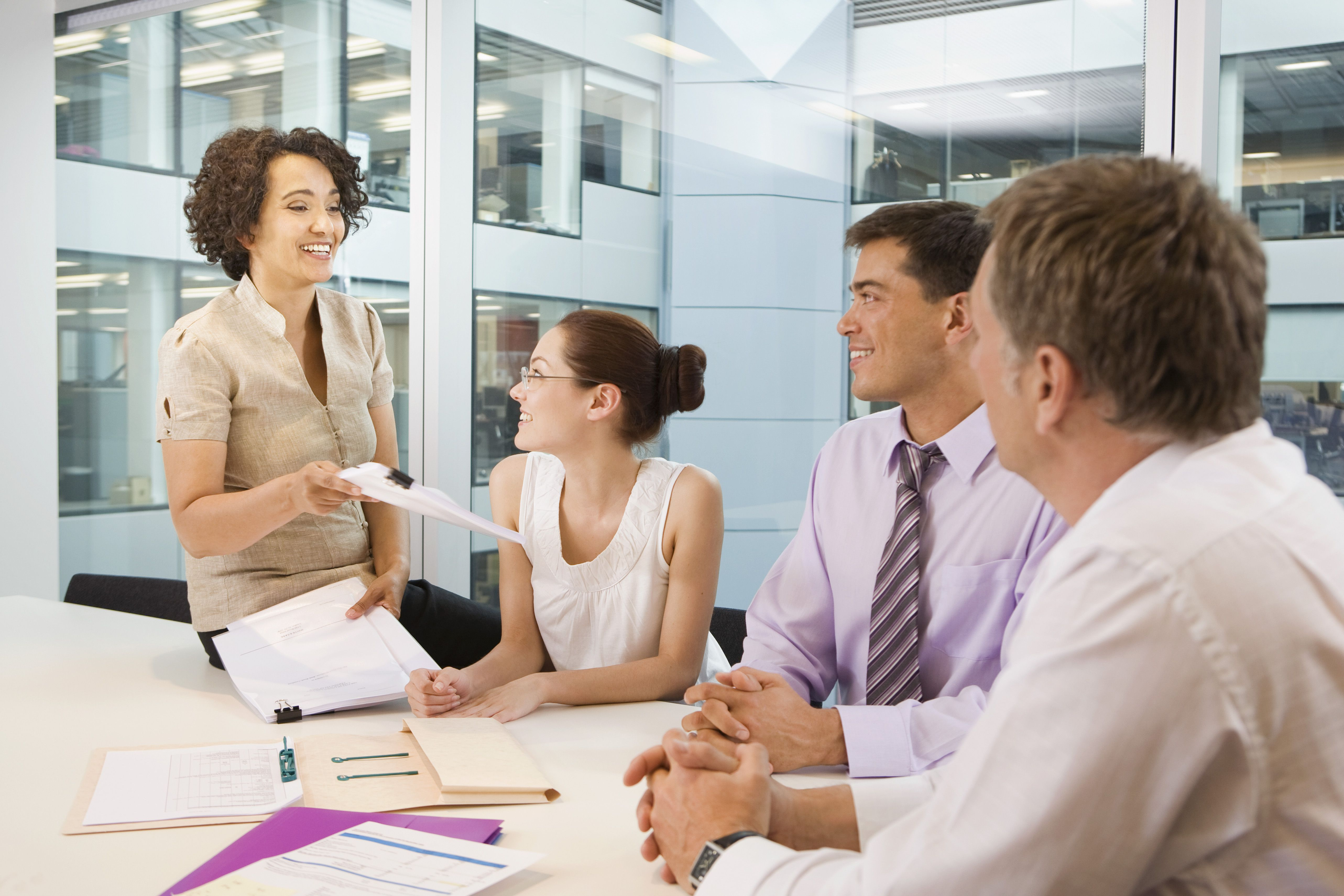 Smiling woman giving coworkers her feedback on a paper.