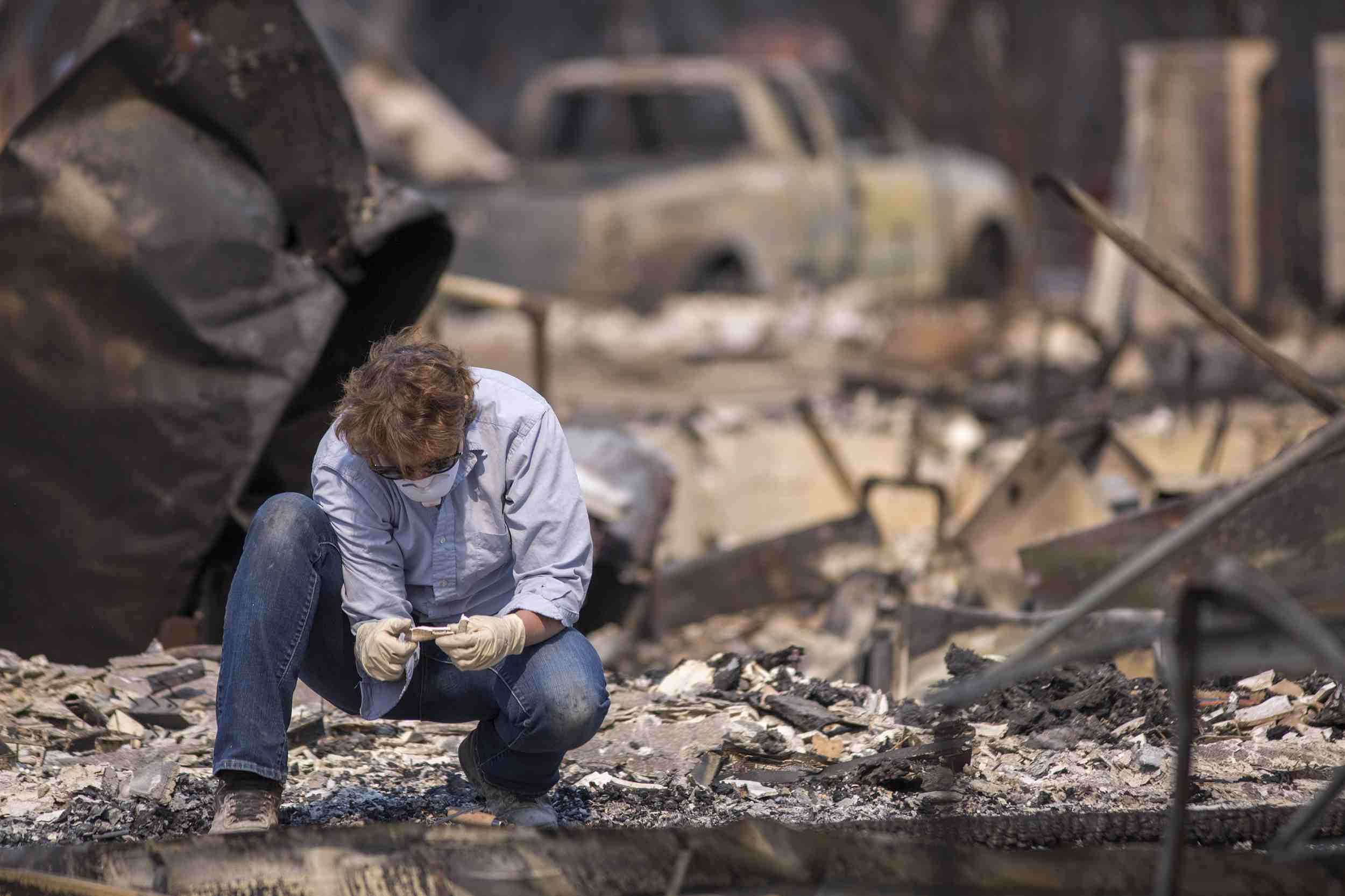 Volunteer forensic anthropologist Alexis Boutinn from Sonoma State University, investigates bones found by California National Guardsmen among fire-devastated homes on October 15, 2017 in Santa Rosa, California.