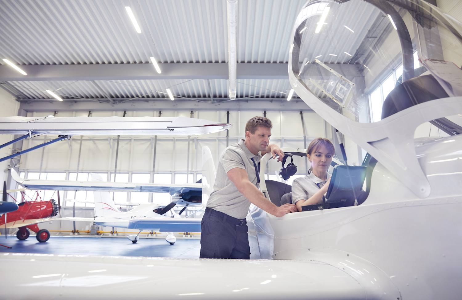 Man and woman working in airplane cockpit in hangar
